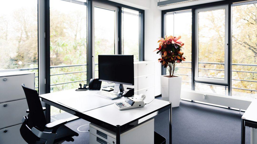 Lichtdurchflutetes, modernes Büro in der Kanzlei mit ergonomischen Möbeln und großen Monitoren.